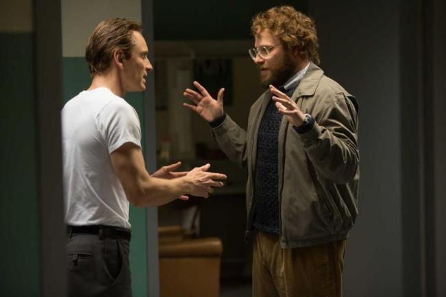 "(L to R) Steve Jobs (MICHAEL FASSBENDER) and Steve Wozniak (SETH ROGEN) in ""Steve Jobs"", directed by Academy Award® winner Danny Boyle and written by Academy Award® winner Aaron Sorkin.  Set backstage in the minutes before three iconic product launches spanning Jobs' career—beginning with the Macintosh in 1984, and ending with the unveiling of the iMac in 1998—the film takes us behind the scenes of the digital revolution to paint an intimate portrait of the brilliant man at its epicenter."
